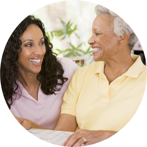 caregiver and old woman smiling at each other